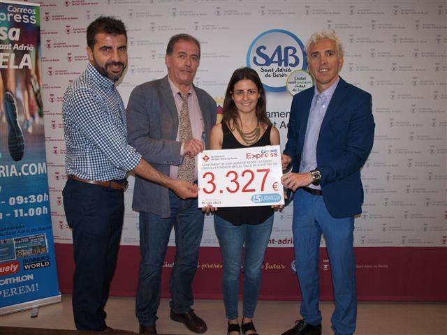 El Alcalde de Sant Adrià de Besòs Joan Callau, Jose Luís Blanco, organizador y Oscar Lozano, representante de Correos Express, entregan un cheque de donativo a la Fundación Miquel Valls.
